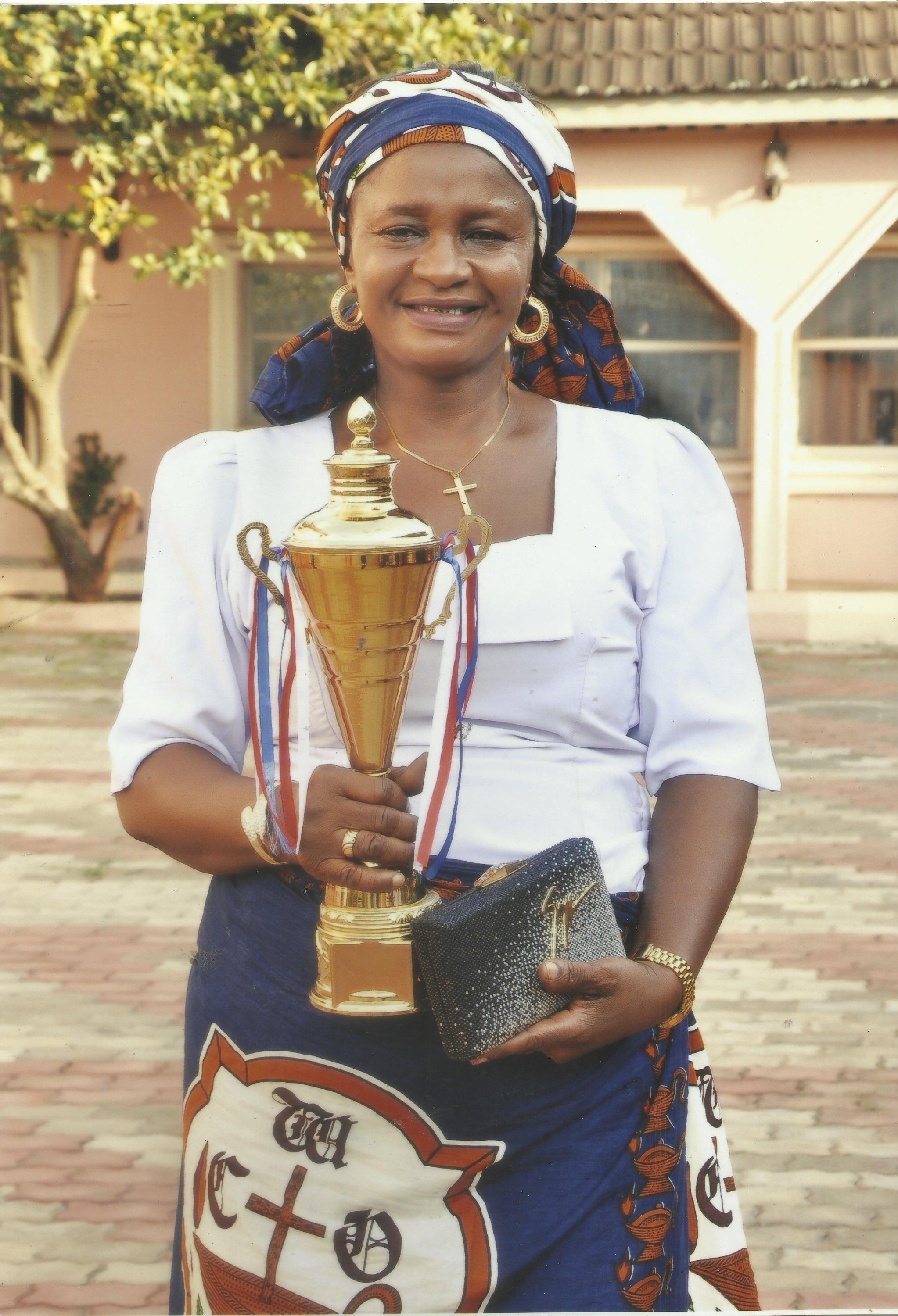 Mum in her CWO attire, holding a trophy